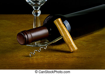 A bottle of wine on the side with a glass and a corkscrew