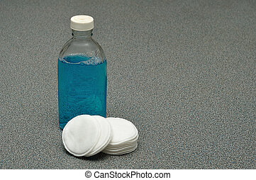A bottle with blue make-up remover and cotton pads