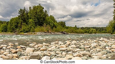 A boulder strewn, fast flowing river, beside a forest, on a cloudy day.