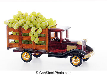 A vintage, wooden, model, pickup truck overflowing with real bunches of juicy green grapes.