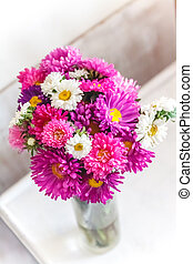 A bouquet of bright colorful flowers asters on a light background