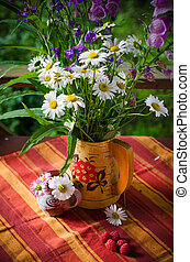 A bouquet of daisies in a jug at the table