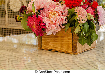 a bouquet of different flowers in a wooden box on the table