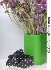 A bouquet of dried flowers is in a plastic glass. Nearby is an open box with a gift. On a white background.