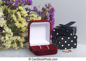 A bouquet of dried flowers lies on a white surface. Next to the box with a gift. Ring and earrings for the beloved.