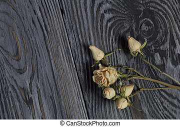 A bouquet of dried roses. Against the background of aged wooden boards with a black structure.