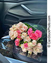 A bouquet of flowers from roses in the front seat of the car