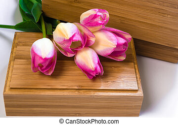 A bouquet of flowers on a white background with wooden crusts. Purple tulips on a wooden box. Place for text. Top view.