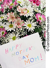 "A bouquet of flowers with a card that says ""Happy Mother's Day Mom"" written in crayon."