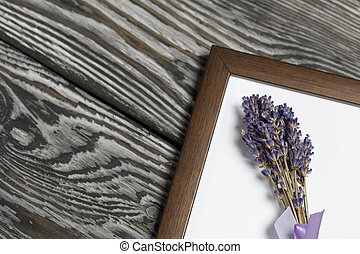 A bouquet of lavender in a photo frame. On brushed pine boards painted black and white.