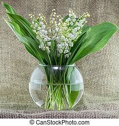 A bouquet of lilies of the valley in a glass vase.