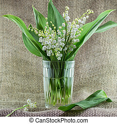 A bouquet of lilies of the valley in a glass vase