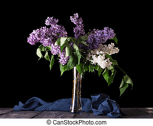 A bouquet of purple and white lilac stands in glass vase, isolated on black