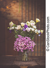 A bouquet of purple flowers in a glass vase on a wooden floor boards of old vintage.