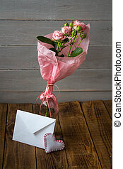 a bouquet of roses in a vase with envelope on wooden background