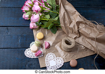 A bouquet of roses is pink, in gray paper and white hearts. Sweet pasta macaroons of different colors, on Valentine's Day. A free place for text or advertising