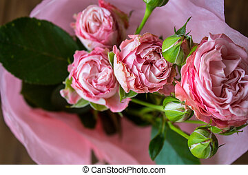 a bouquet of roses on wooden background