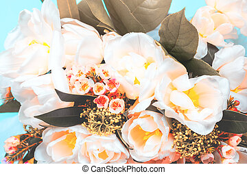 A bouquet of tulips and decorative flowers close-up on a blue background.