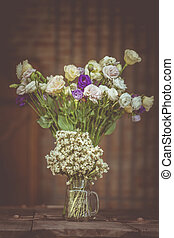A bouquet of white flowers in a glass vase on a wooden floor boards of old vintage.