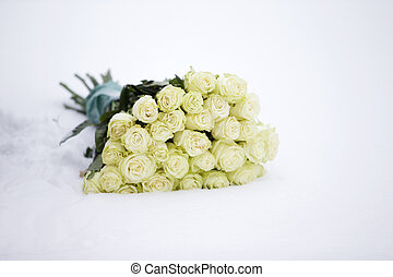 A bouquet of white roses in the snow