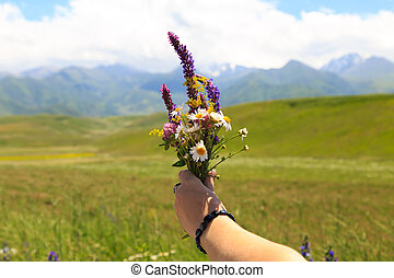 A bouquet of wild flowers in the girl's hand. Against the background of high mountains.