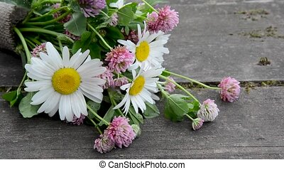 A bouquet of wildflowers lies on a wooden table.