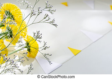 A bouquet of yellow chrysanthemums lies on a white table surrounded by a garland of flags.