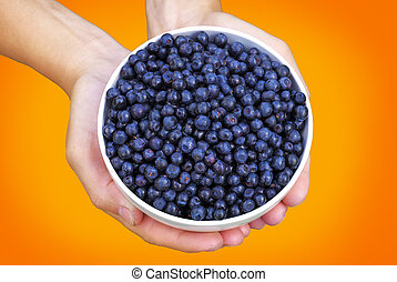 A bowl of blueberries in hands on orange background