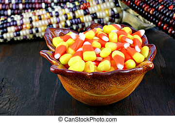 A bowl of candy corn on rustic wooden table
