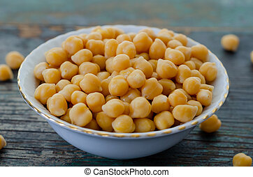 A Bowl of cooked chickpeas on the wooden table -, close up