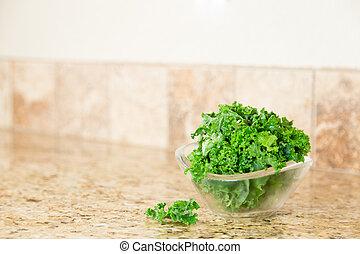 A bowl of fresh green kale on a granite countertop