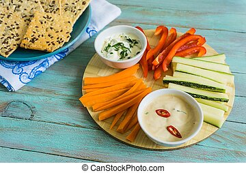 a bowl of fresh vegetables and dips. a healthy concept