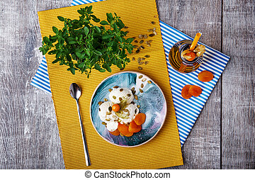 A bowl of ice cream, a bottle of apricot juice and decorative tree on a wooden background. Top view of a light dinner.