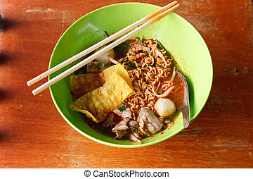 A bowl of noodles with soup.