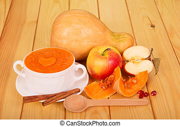 A bowl of pumpkin puree, whole pumpkin and apple, slices, cinnamon sticks, pomegranate seeds and a spoon on light wood.