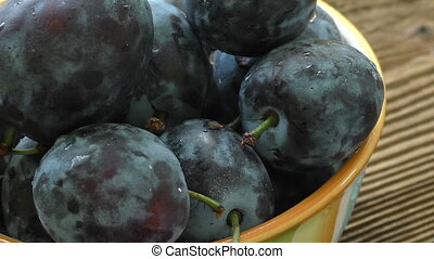 A bowl of ripe blue plums on a dark wooden background