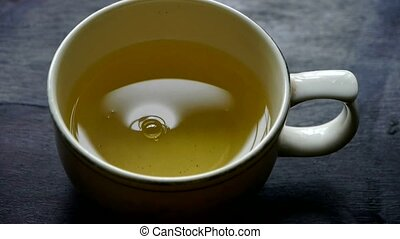 A bowl of steaming tea. china, water.
