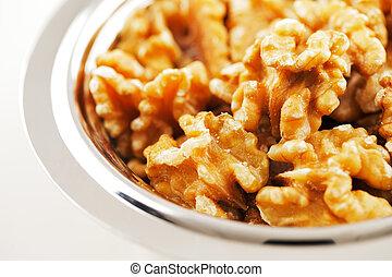 A bowl of walnut seeds on white bac