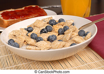 A bowl of wheat cereal with blueberries, toast and orange juice