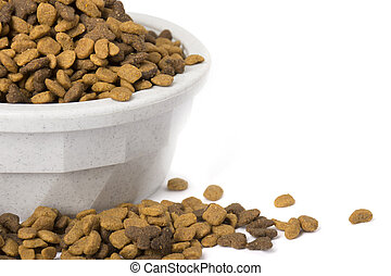 A bowl with dry cat food overflowing out of the bowl