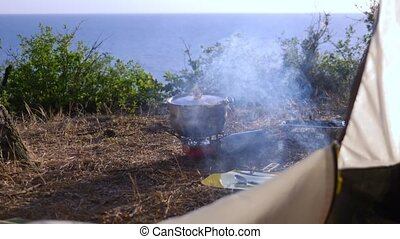 a bowler and a disposable grill. cooking next to a tent on...