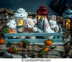 A box of toys sits on a sofa covered with a warm plaid blanket. Burning lanterns create an atmosphere of comfort
