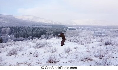 A boxer trains in the mountains in the fresh air. He works...