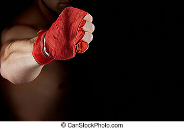 A boxer's red bandage on his hand isolated on dark blurred background, close-up.