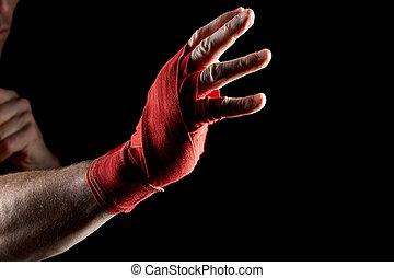 a, boxer's, rotes , verband, auf, seine, hand, freigestellt, auf, dunkel, unscharfer hintergrund, close-up.