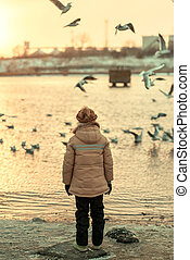 a boy and a bird on the river