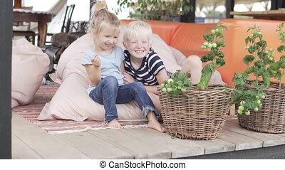 Cute brother and little sister hugging on a beautiful veranda in summer