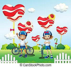 A boy and a girl biking near the giant lollipops