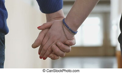 A boy and a girl holding hands with love