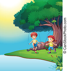 A boy and a girl playing near the giant tree
